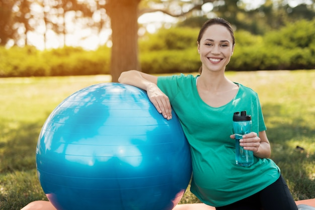 Pregnant girl sits at yoga mat and holds yoga ball.