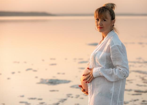 ビーチに立って、お腹に触れている妊婦。カメラを見て