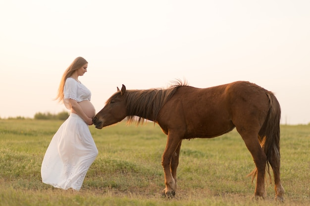 A pregnant girl in white communicates with a horse on a green meadow at sunset. therapy and relaxation for pregnant women. antistress therapy.
