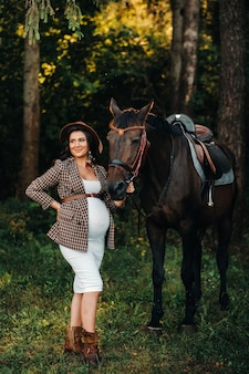 Pregnant girl with a big belly in a hat next to horses in the forest in nature.stylish girl in white clothes and a brown jacket.