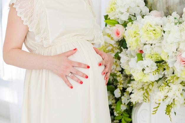 背景に花を持つ妊娠中の女の子