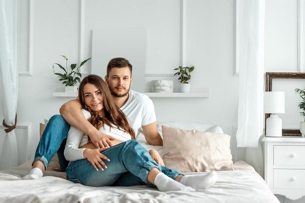 그녀의 남편과 임신 한 여자는 침대에 누워. 젊은 매력적인 임신 한 여자의 아름 다운 배꼽입니다. 가족, 결혼, 출산 개념.