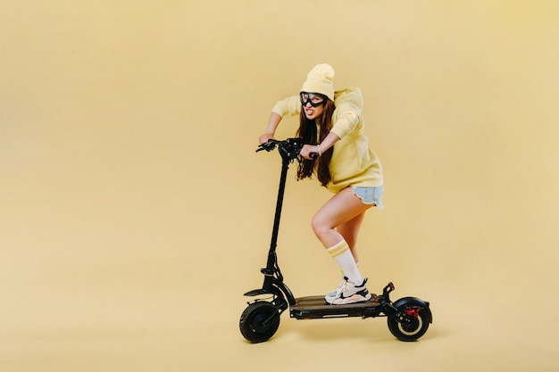 A pregnant girl in yellow clothes on an electric scooter on an isolated yellow background.