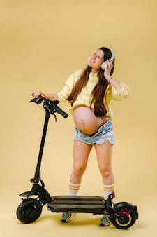 Pregnant girl in yellow clothes and headphones on an electric scooter on an isolated yellow background.