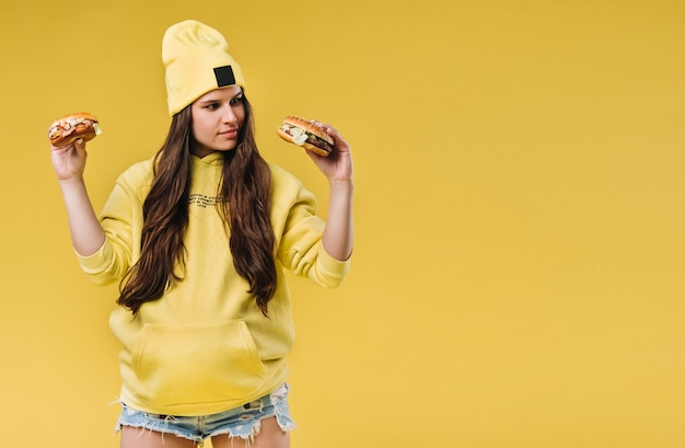 Pregnant girl in yellow clothes with hamburgers in her hands on a yellow background