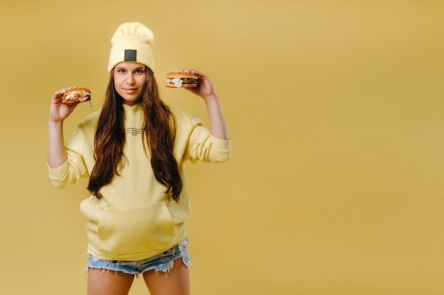 Pregnant girl in yellow clothes with hamburgers in her hands on a yellow background.