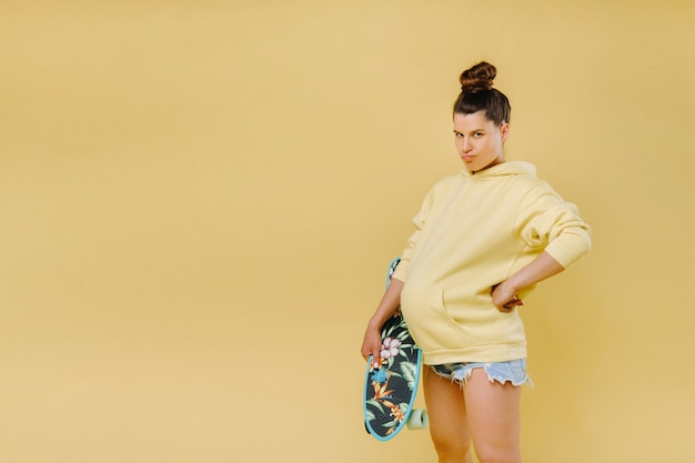 Pregnant girl in a yellow jacket with a skateboard in her hands on a yellow background