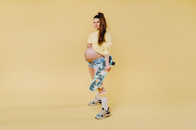 Pregnant girl in a yellow jacket with a skateboard in her hands on a yellow background.