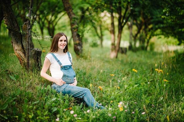 Беременная счастливая девушка держится за руки на животе, сидя на траве в поле на открытом воздухе в саду