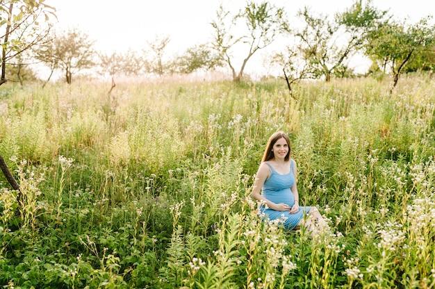 妊娠中の幸せな女の子が座っているし、胃の手を握って、屋外の庭のフィールドの芝生の上に座っています。