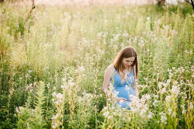 妊娠中の幸せな女の子は、屋外のフィールドで表面の緑の芝生に座って、お腹に手をつないで座っています