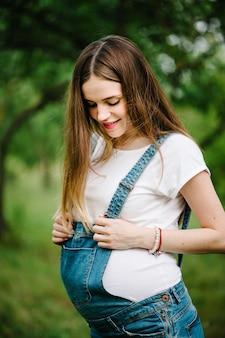 Беременная счастливая девушка стоит и держится за руки на животе, стоит на открытом воздухе в саду