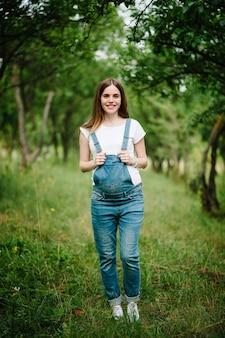 妊娠中の幸せな女の子は立って胃に手を握り、木々のある庭の表面の屋外の草の上に立つ