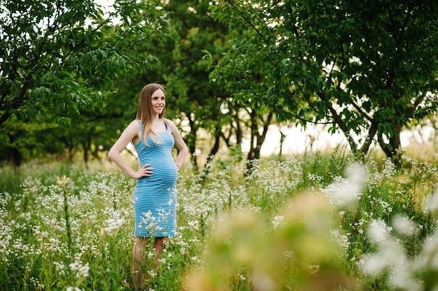 妊娠中の幸せな女の子立って、胃に手を繋いで、屋外の庭の芝生の上に立つ