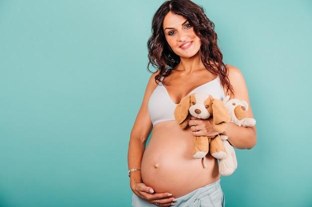 아이를 기대하는 임신한 행복한 여자가 그녀의 배를 애무한다