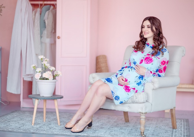 Pregnant happy woman sits in an armchair