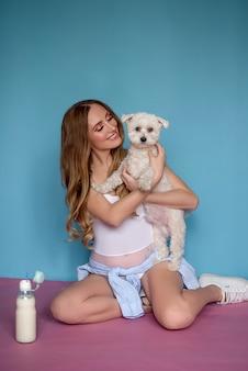 Беременная счастливая женщина с собакой на синем фоне