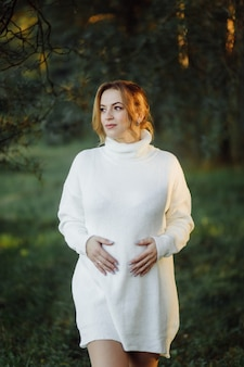 Pregnant happy young woman walking outdoors in forest