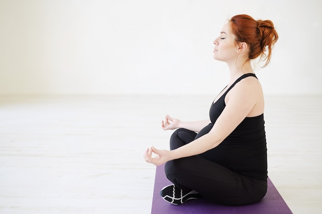 Pregnant healthy woman meditating with closed eyes