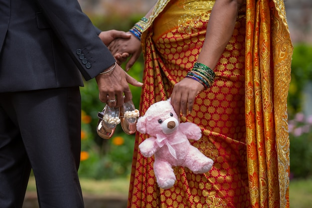 Pregnant indian woman and her husband  holding baby toys