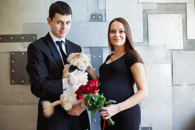 Pregnant loving couple together with cat