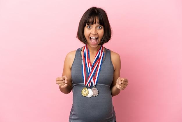 우승자 위치에서 승리를 축하하는 분홍색 배경에 격리된 메달을 가진 임신한 혼혈 여성