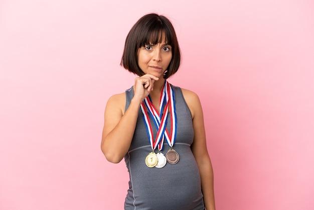 의심과 생각을 가지고 분홍색 배경에 고립 된 메달을 가진 임신 혼혈 여성