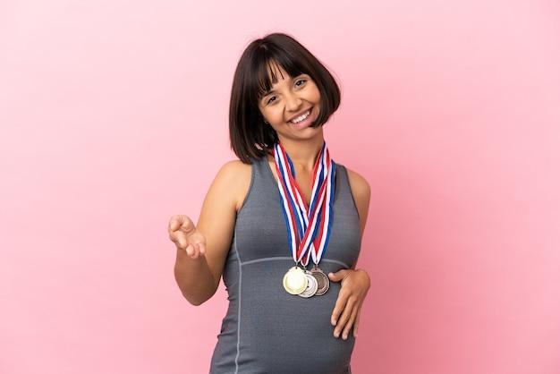 분홍색 배경에 격리된 메달을 가진 임신한 혼혈 여성이 좋은 거래를 성사시키기 위해 악수