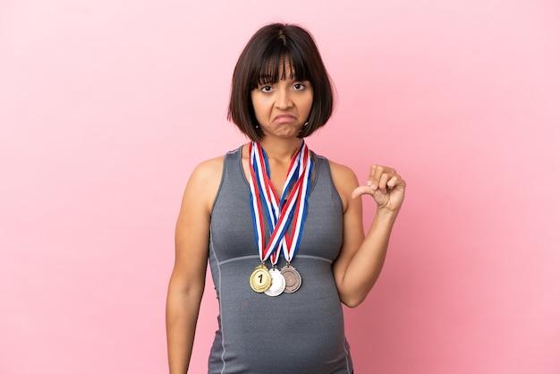 분홍색 배경에 격리된 메달을 가진 임신한 혼혈 여성이 부정적인 표정으로 엄지손가락을 아래로 내리고 있습니다.
