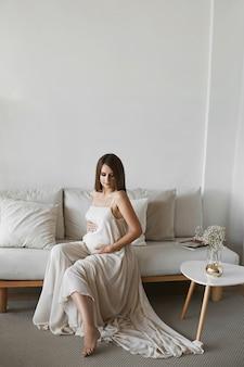 Беременная модель девушка держит с любовью ее живот и позирует в минималистском интерьере. концепция беременной моды