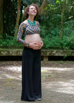 Pregnant modern young woman touching her belly and looking to the sky outdoors.