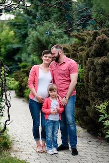 임신 한 엄마, 딸, 아빠가 공원을 걷고 있습니다.