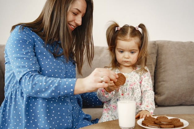 Pregnant mom in a dress. girl drinks milk. mom and daughter enjoy cookies.