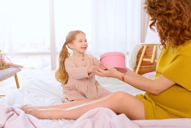 妊娠中のお母さんは娘と遊んでいます。家族、喜び、妊娠の概念