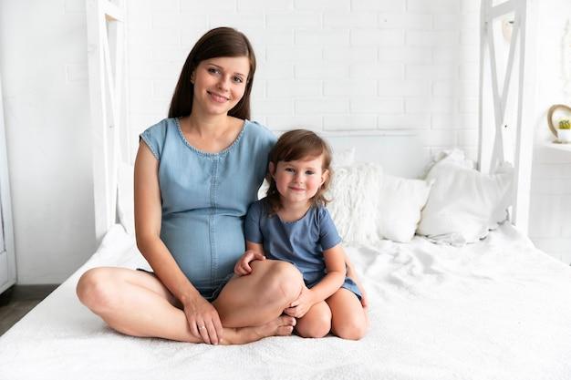 Беременная мать и дочь смотрят в камеру