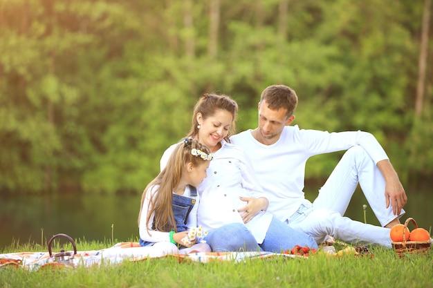 晴れた日の公園でのピクニックで妊娠中の母親と幸せな父と幼い娘。写真にはテキスト用の空きスペースがあります