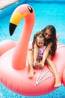 임신 어머니와 그녀의 딸은 풍선 핑크 플라밍고에 떠 있었다