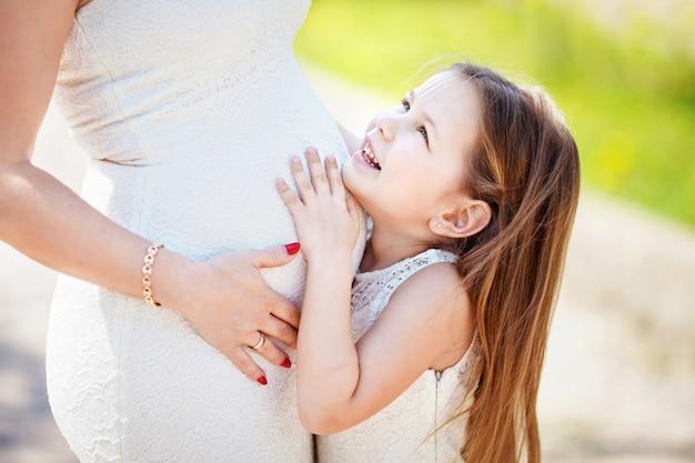 Беременная мать и ее маленькая дочь весело проводят время на открытом воздухе.