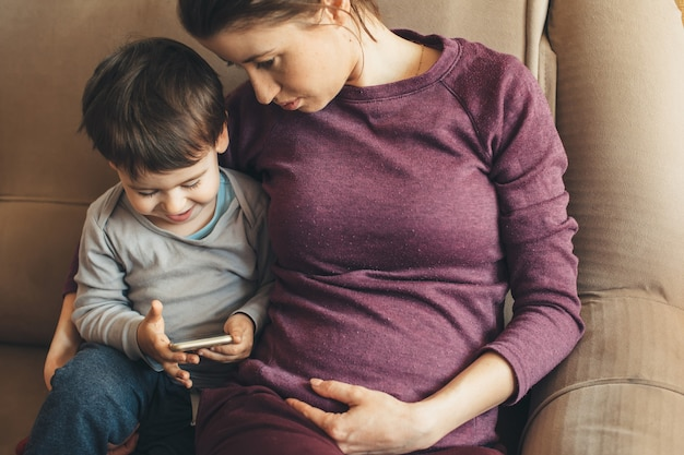 Беременная мать и ее сын разговаривают по мобильному телефону и сидят на диване