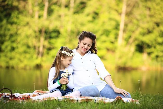 Беременная мать и маленькая дочь на пикнике в парке в солнечный день. на фотографии есть пустое место для вашего текста