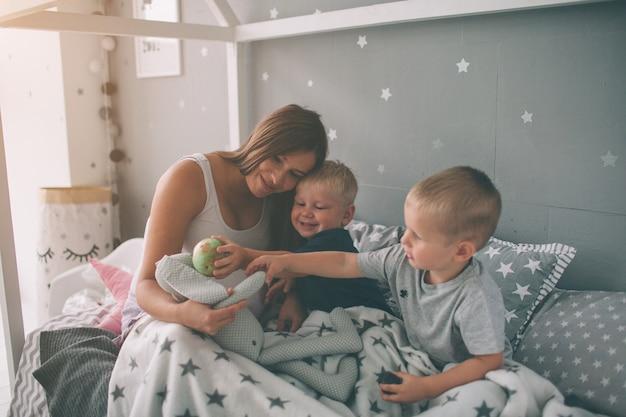 Беременная мама и двое сыновей утром читают дома интересную книгу. повседневный образ жизни в спальне