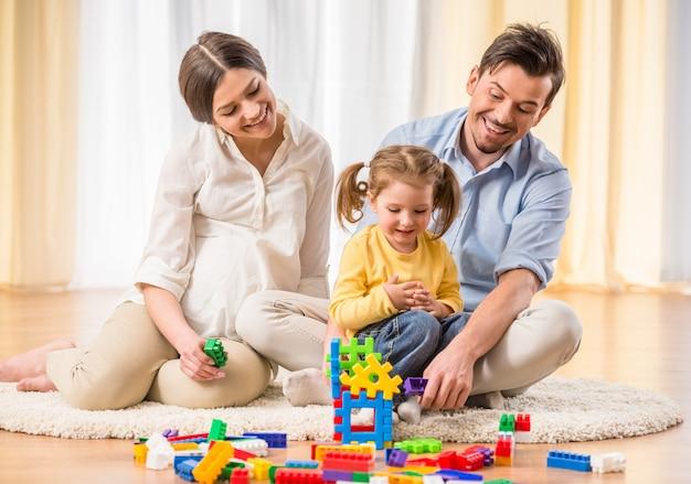 임신 어머니와 젊은 아버지는 딸과 함께 놀고있다.