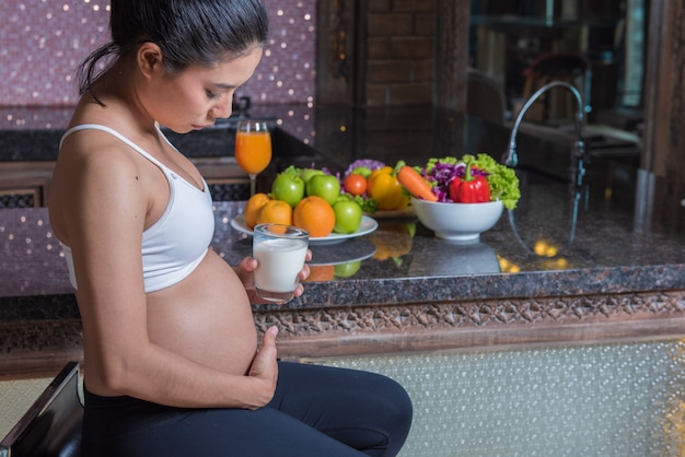 Pregnant mother drinking milk with fruits