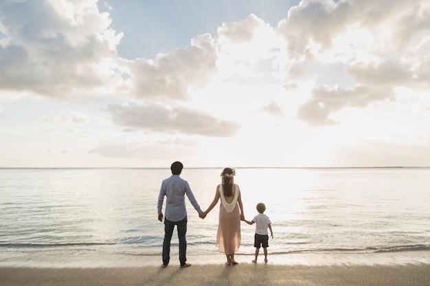 임신 어머니 아버지와 아들 해변에서 석양을 기쁘게 생각합니다.