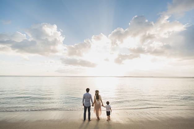 해변에서 임신한 어머니 아버지와 아들은 일몰을 기뻐했습니다.