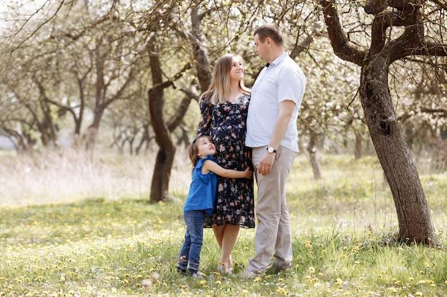 임신 한 어머니, 아버지 손을 잡고 딸 자연을 즐기고 봄 피는 공원에서 산책.