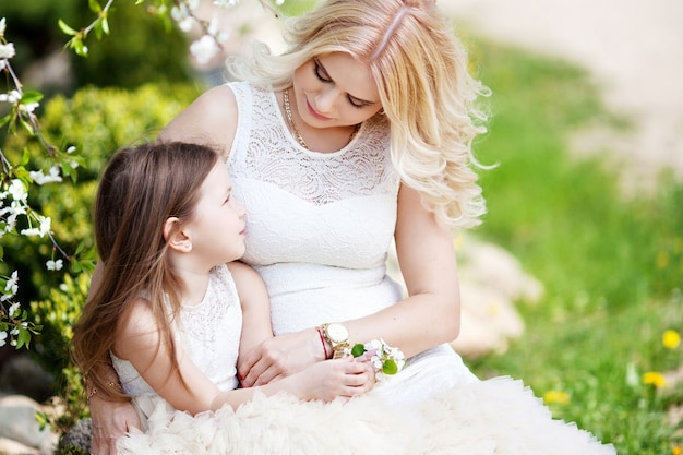 Pregnant mother and her small daughter have fun outdoor. family look portrait