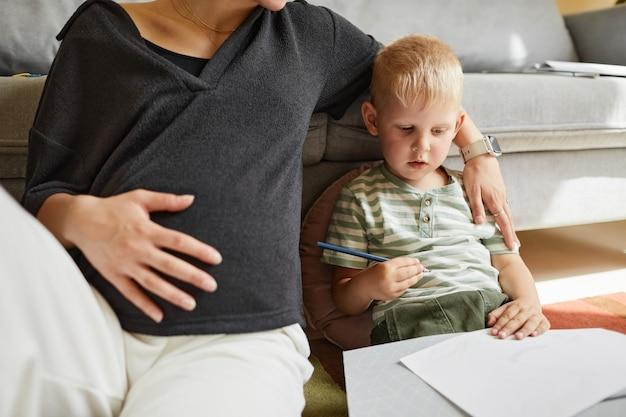 Беременная мать, взявшись за руки на животе, сидя с сыном на полу и рисуя картину