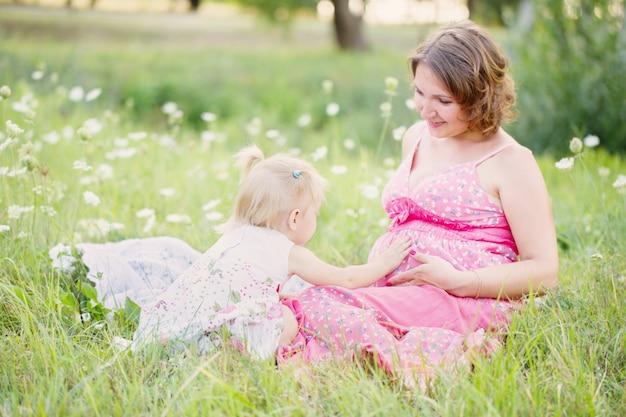 Беременная мать играет со своей дочерью на открытом воздухе