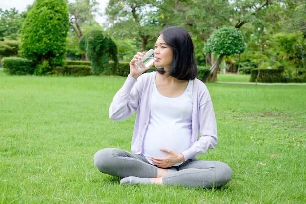Беременная мать сидит и пьет чистую воду в стакане для здоровья.